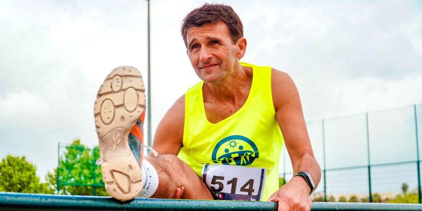 Възрастен мъж тренира тичане и прави стречинг