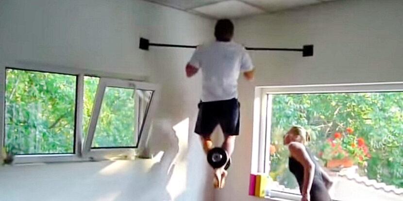 Мъж изпълнява набиране на лост с допълнителна тежест в краката