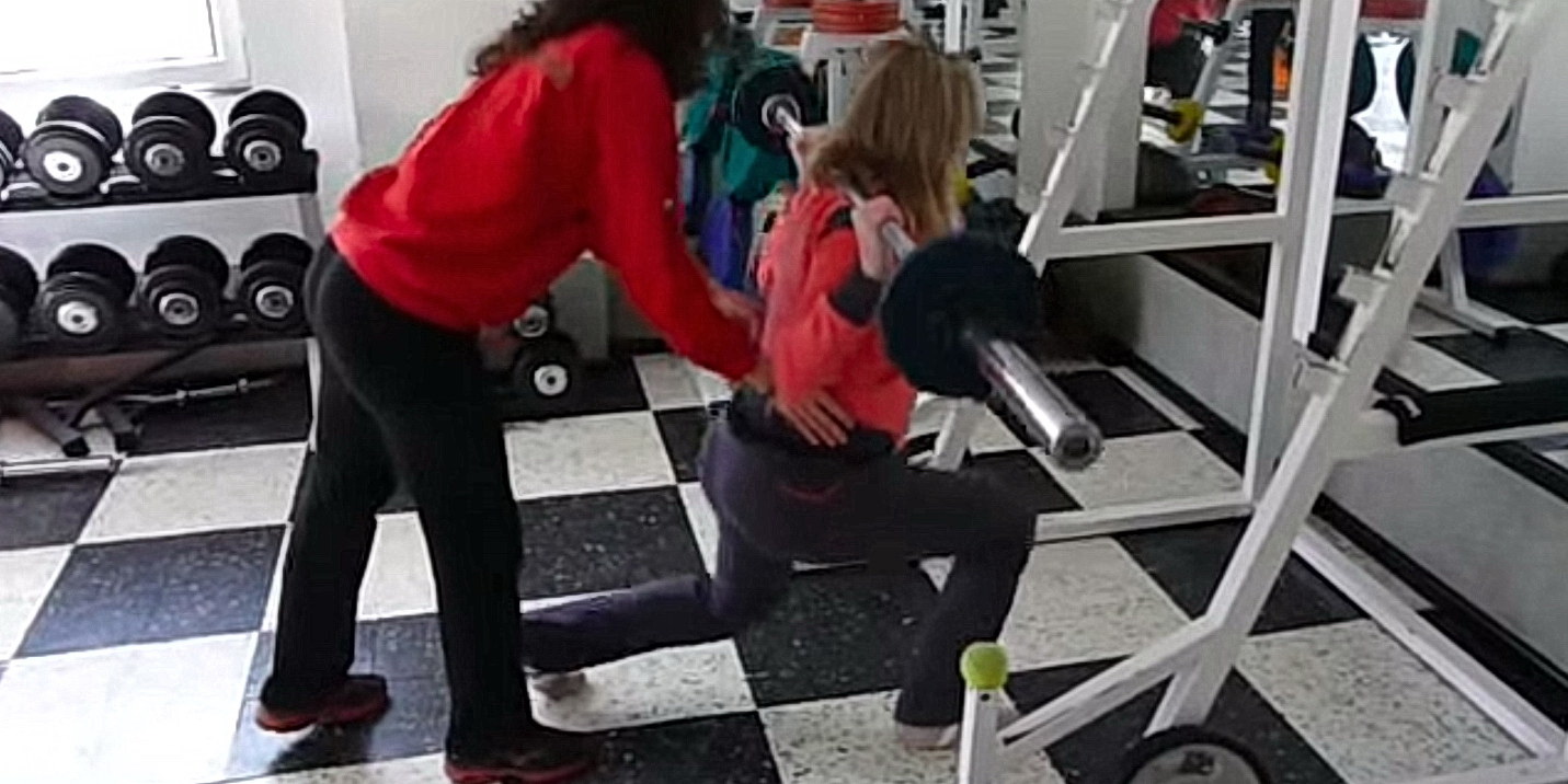 Бременна жена тренира с тежести и прави напади с щанга